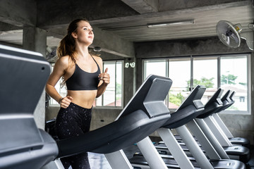 Cute young woman exercising on  treadmill at a gym.Active young woman running on treadmill. smile and funny emotion.