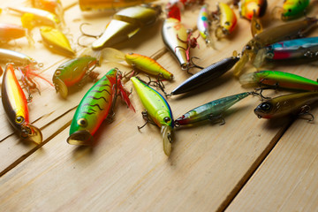Various of fishing lures on wooden background.