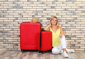 Woman with suitcases near brick wall. Vacation travel