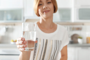 Woman holding glass with clean water in kitchen, closeup