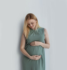 Young pregnant woman touching belly on light background