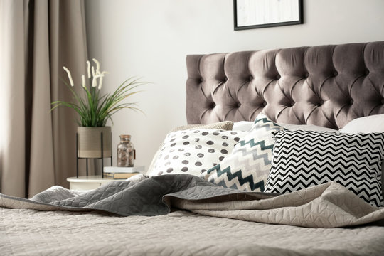 Comfortable bed with cushions in stylish bedroom interior