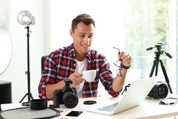 Portrait of photo blogger with cup of coffee and laptop at home. Online broadcast