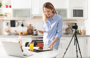 Food blogger taking photo of breakfast in kitchen