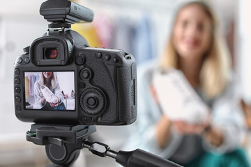 Fashion blogger recording video indoors, selective focus on camera display. Space for text