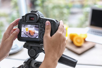 Blogger taking photo of food with professional camera indoors