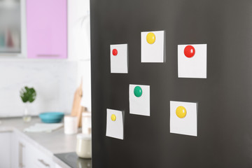 Blank paper notes and magnets on refrigerator door in kitchen