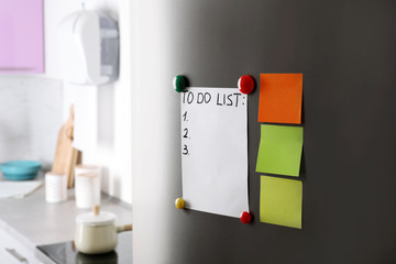 Paper notes, to-do list and magnets on refrigerator door in kitchen