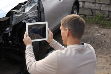 Man taking photo of broken car after accident for insurance claim