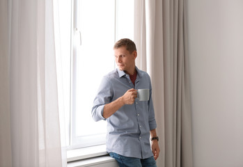 Mature man near window with open curtains at home