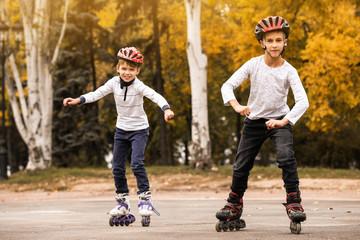 Happy children roller skating in autumn park