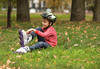 Cute boy with roller skates sitting on grass in park