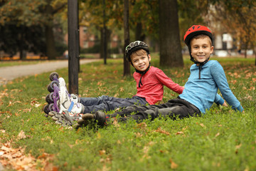 Cute roller skaters sitting on grass in park