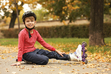 Cute boy with roller skates sitting on road in park