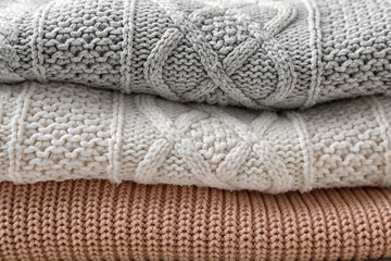 Fototapete - Stack of folded warm knitted sweaters, closeup