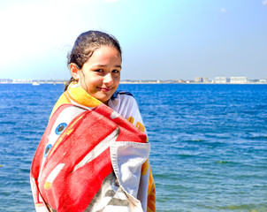 Woman with towel on the beach while sunbathing. cute little girl covered with towel at summer beach