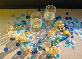 Sektgläser mit Sekt auf der Fensterbank bei Sonnenschein mit blauem Konfetti,  gelben Luftschlangen und Rollpfeifen