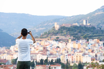 A tourist is taking a picture with his phone at the beautiful and colorful village of Bosa  located in the north-west of Sardinia, Italy.