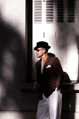 Elegant man with retro look and hat and sunglasses on the street