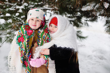 two little girls in fur coats and Russian scarves on the background of snow-covered trees