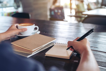 Closeup image of a woman holding and drinking hot coffee while writing on notebook on wooden table in cafe