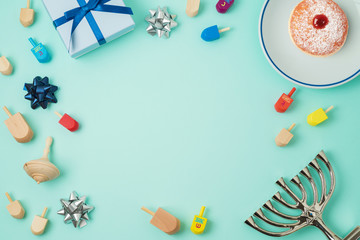 Jewish holiday Hanukkah background with menorah, sufganiyot, gift box and spinning top.