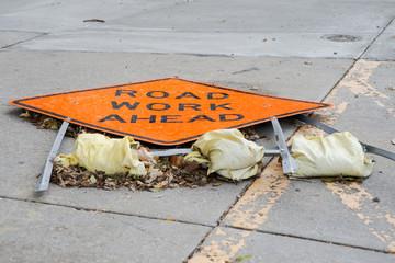 Broken Road Work Ahead sign on concrete sidewalk during roadwork.