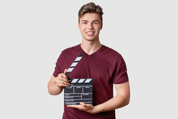 Positive young guy with muscular body, wears casual outfit, holds clapper board, looks at camera with toothy smile, stands indoor against white background. Film making, cinematography concept
