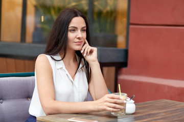 Dreamy pensive woman with dark hair, dressed in formal clothes, drinks cocktail, spends free time in outdoor cafeteria, focused into distance. People, leisure, spare time and lifestyle concept