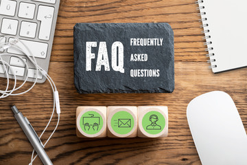 """Slate plate with text """"FAQ - frequently asked questions"""" on wooden background"""