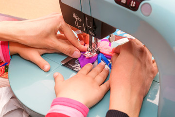 Adult seamstress teaches a child to sew on a sewing machine. Close-up
