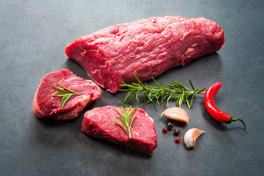 Whole piece of tenderloin with steaks and spices ready to cook on dark background