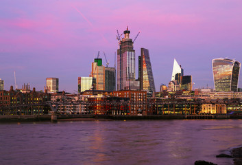 purple sunset scenery of Thames river and modern buildings in London city United Kingdom