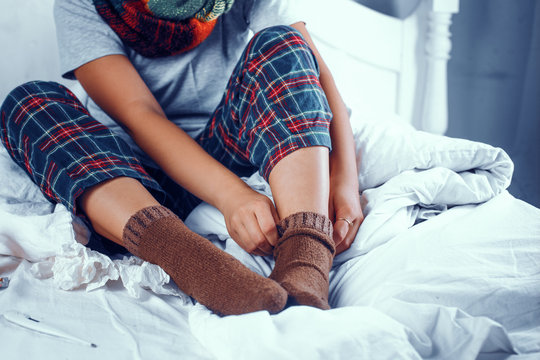 Girl is coloured scarf and checkered pants puts on brown cotton socks while sitting in bed.