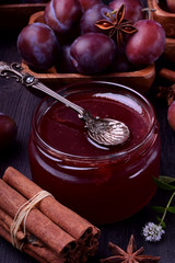 Plum jam in a glass jar surrounded by the berries