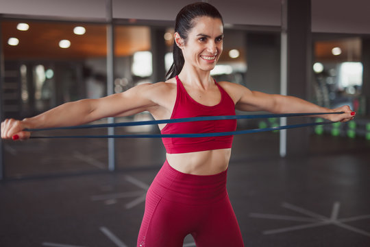 Cheerful woman stretching exercise band