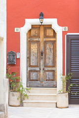 Presicce, Apulia - An old wooden door and a bordeaux facade