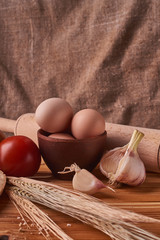 fresh delicious bread, concept for baking. Eggs in clay bowl, garlik, tomato and wheat sprouts on wooden table
