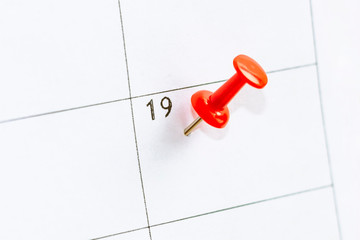 19 date pinning on calendar with Red color pin thumbtack. Save the Date concept.