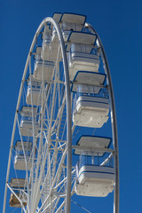 Giant ferris wheel with chairs, metallic structure, recreational element near the river