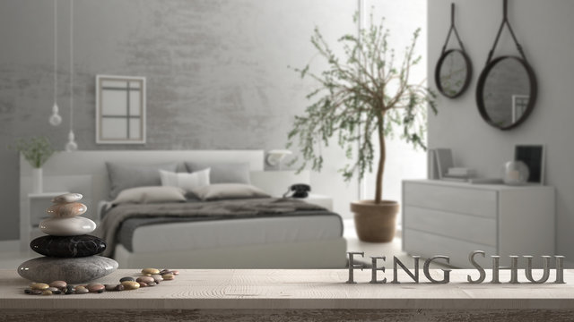 Wooden vintage table shelf with pebble balance and 3d letters making the word feng shui over blurred bedroom with window, chest of drawer and big olive tree, zen concept interior design