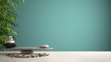Empty interior design feng shui concept zen idea, white table or shelf with pebble balance and green bamboo, over turquoise background copy space