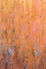 Peeling pink and orange paint on decaying wood panel fence/door