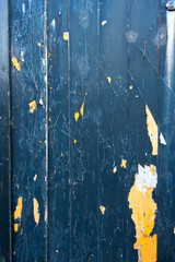 Peeling blue and yellow paint on decaying wood panel fence/gate