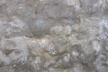 Details of grey rendered lumpy stone wall with small cracks and white flecks