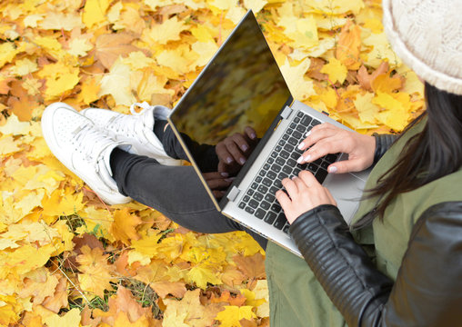 Girl in hipster with laptop in autumn park. A woman in a cap using a laptop while sitting on fallen leaves. Freelancer in the hat uses remote communication technology. Remote work. View from above