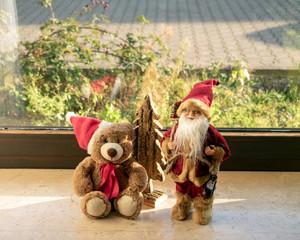 Weihnachts-Teddy und Weihnachtsmann auf der Fensterbank
