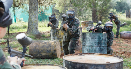 Two active opposing teams with guns playing paintball against each other  outdoors