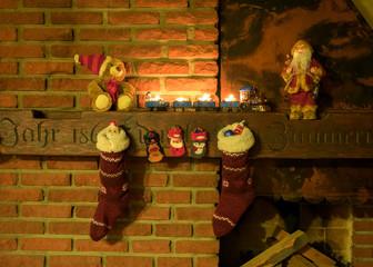festlich geschmückter, rustikaler Kamin mit gefüllten Weihnachtsstrümpfen