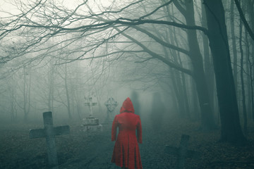 ghost woman in red dress on dark horror forest cemetery